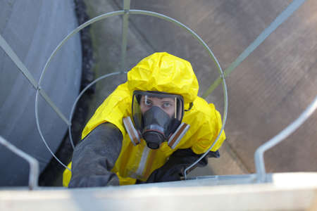 welly: technician in protective uniform going up a metal ladder on storage tank