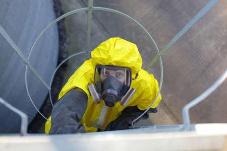 Techniker in schützenden Uniform gehen auf einen Metall-Leiter auf Speicher Standard-Bild