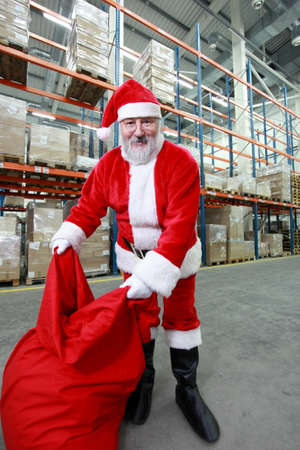 Happy Santa Claus with red sack in storehouse photo