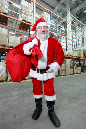 commercialization: Happy Santa Claus with red sack in storehouse Stock Photo