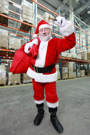 commercialization: Santa Claus with red sack ringing in a bell in storehouse Stock Photo
