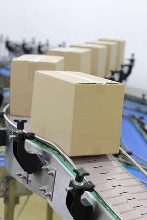 Kartonnen dozen op een transportband in de fabriek Stockfoto