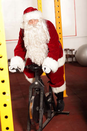 Santa Claus training on exercise bikes in gym photo