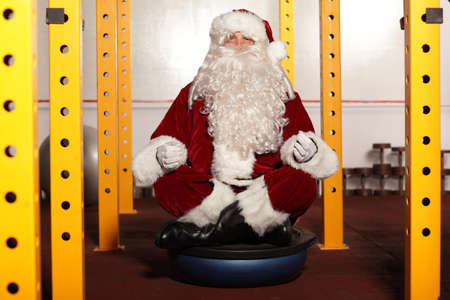 Santa Claus sitting in yoga position on fitness hemiball photo