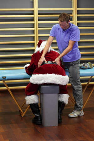 male therapist massaging overworked Santa Claus photo