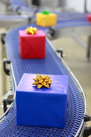 Gifts on conveyor belt in Christmas presents factory