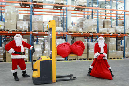 two santa clauses workers at work in large storehouse photo