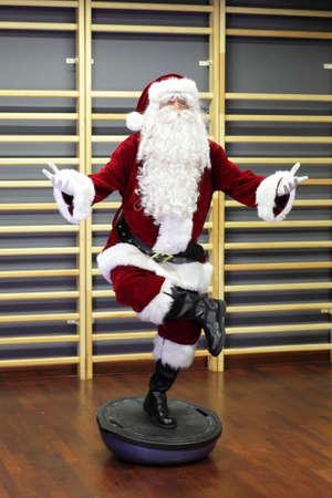 Santa Claus Fitnesstraining auf stablity Hemisphäre Lizenzfreie Bilder