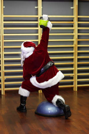 Santa Claus kettlebells training, back view photo