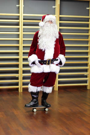 Santa Claus standing on skateboard in fitness studio photo
