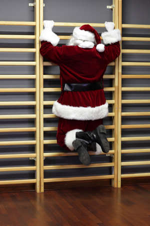wall bars: santa claus exercising with wall bars,Christmas Time preparation Stock Photo