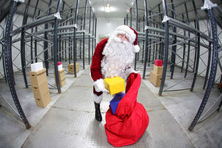 irony: Santa Claus preparing for Christmas in storehouse Stock Photo