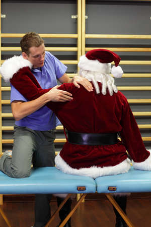 senior man on a neck pain: male therapist massaging stressed Santa Claus
