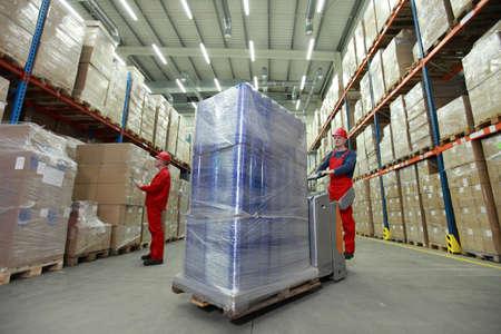 palet: almacenamiento - la gesti�n de los flujos de recursos - dos trabajadores en los uniformes y cascos de seguridad que trabajan en almac�n