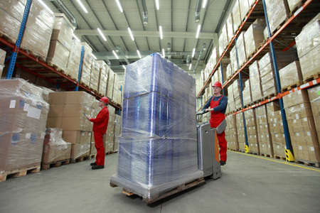 warehousing: warehousing - management of the flow of resources - two workers in uniforms and safety helmets working in storehouse  Stock Photo