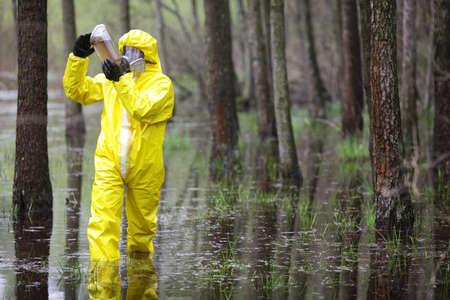 contaminacion del agua: totalmente protegida con el uniforme, botas, guantes y técnico de la máscara muestra el examen de agua en un recipiente de plástico en la zona de las inundaciones