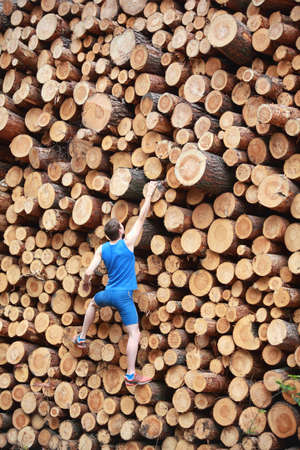 individual sport: Fit climber going up the large pile of cut wooden logs