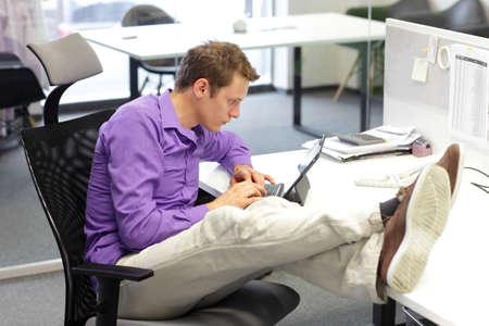productividad: Joven empresario de raza caucásica en su oficina de trabajo con tableta - mala postura al sentarse Foto de archivo