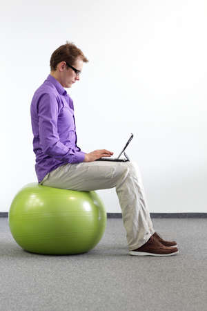 proper: man on stability ball working with tablet - correct sitting position Stock Photo