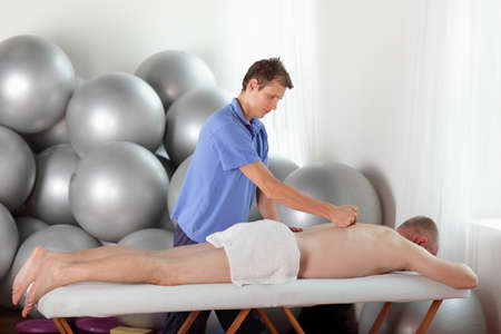 massage table: male therapist massaging middle age caucasian man s back