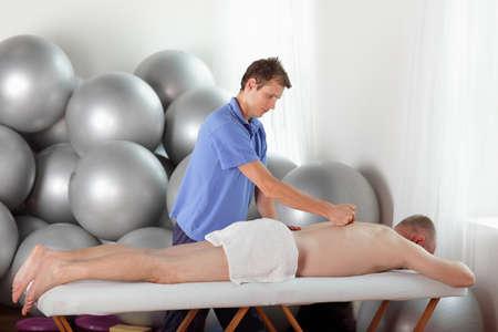 masaje deportivo: terapeuta masculino masaje edad media de la espalda, caucásico, hombre s Foto de archivo