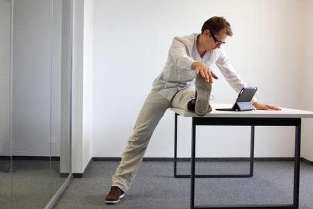 Beinübung durrng Büroarbeit - Mann liest auf Tablet in seinem Büro