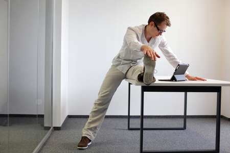 stretching exercise: leg exercise durrng office work - man reading at tablet in his office