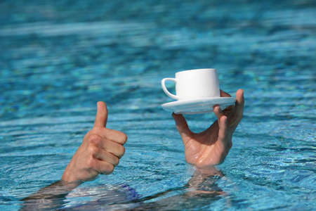 pool symbol:  thumb up gesture - hand above water holding cup of coffee