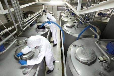 Twee specialisten in witte beschermende overall en veiligheidsbril werken met industrieel proces tank in de fabriek Stockfoto