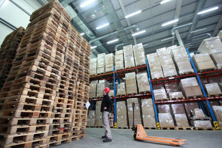 euro pallet: worker with hand pallet truck at large  stack of wooden pallets in storehouse Stock Photo
