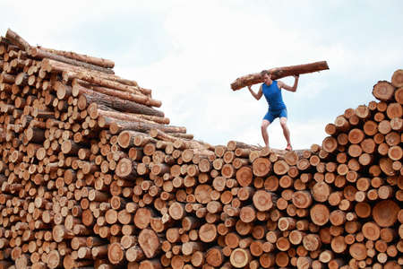 will power: man on top of large pile of logs, lifting heavy log - training