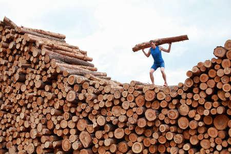 Mann an der Spitze von großen Stapel von Baumstämmen, Heben schwerer log - Ausbildung