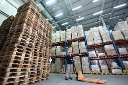 worker with hand pallet truck at large  stack of wooden pallets in storehouse Standard-Bild