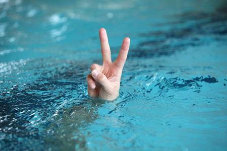believe: El lenguaje corporal de la mano con dos dedos hacia arriba en la victoria o el símbolo de la paz, por encima de la superficie del agua