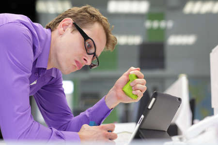 Stressed business man  looking at screen of tablet in office squeezing stress  sponge photo