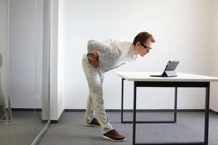 exercise durrng office work - man with tablet in his office photo