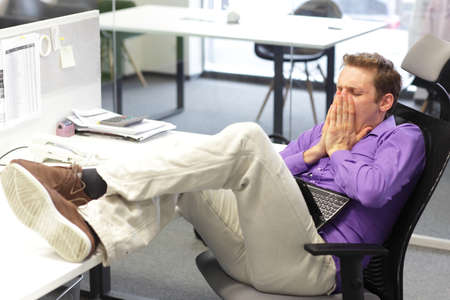office force: Young tired  businessman yawning over his tablet in office