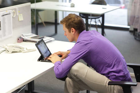 malos habitos: hombre de negocios en la oficina se inclinó sobre una tableta - mala postura al sentarse Foto de archivo