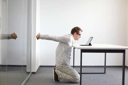 ストレッチ - タブレット彼のオフィスでの作業中に演習を行う人間の武器