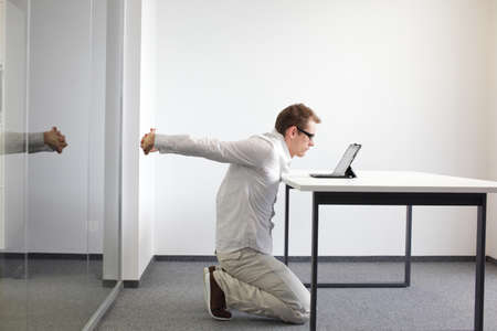 stretching exercise: arms stretching - man doing exercises during work with tablet in his office