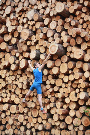 Fit climber going up the large pile of cut wooden logs photo