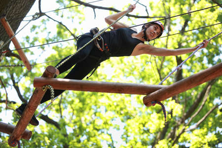Young attractive woman climbing in adventure rope park in mountain helmet and safety equipment