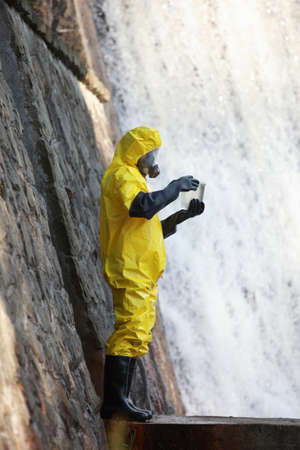 toxicology: fully protected in coveralls ,boots,gloves and mask scientist examining sample of water of water Stock Photo
