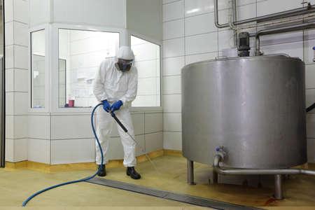 trabajador en uniforme de protección blanca, máscara, guantes con lavadora de alta presión a la gran planta de limpieza de tanques de proceso industrial en la planta de