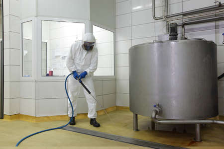 welly: worker in white protective uniform,mask,,gloves  with high pressure washer at  large industrial process tank  cleaning floor  in plant Stock Photo