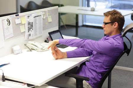 productividad: Hombre trabajador de oficina, hacer ejercicio durante el trabajo con la tableta en su oficina