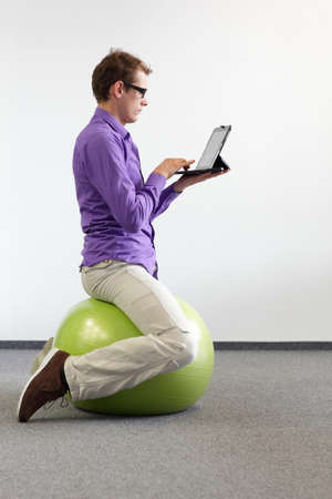 man on stability ball working with tablet - correct sitting position Standard-Bild