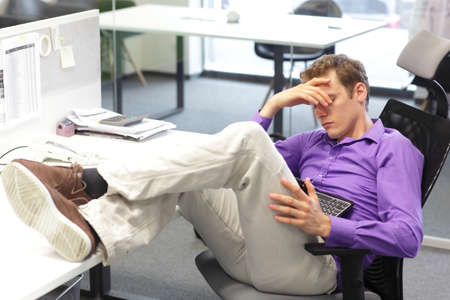 Young businessman snoozing over his tablet in office