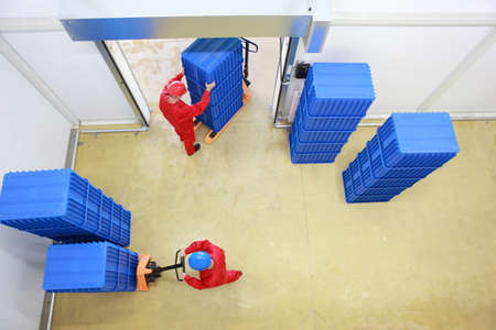 stocktaking: Aerial view of two workers working with plastic blue boxes in small warehouse