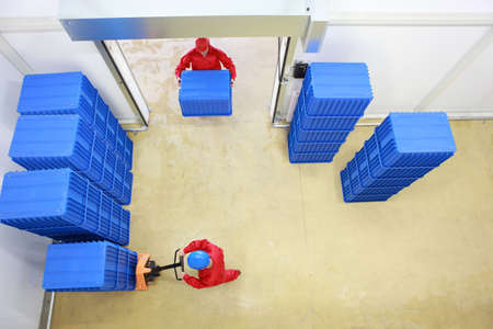 Aerial view of two workers working with plastic blue boxes in small warehouse  photo
